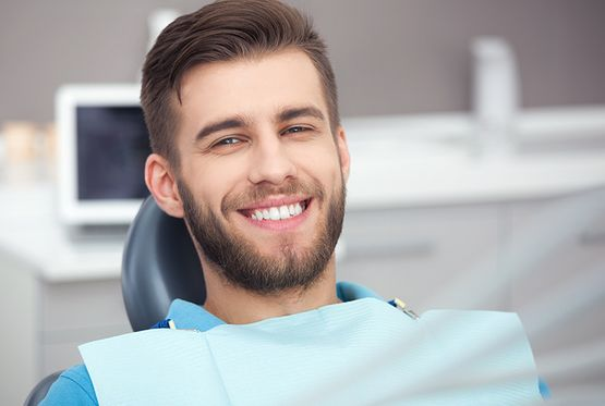 Patient smiling in a dental chair after receiving dental implant restoration from Dr. James A. Vette, DDS in Germantown, MD
